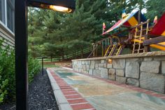 The rear hardscape consists of CMU walls with a Stoneyhurst veneer stone topped with Teakwood caps; natural cleft gold quartzite stone wet laid on concrete; a Raffinato smooth border in beige cream color installed along walkway. The playground area was laid out with safe mulch and owner supplied playground set. The project was completed with lighting and plantings. Playground Set, Stone Veneer, Landscape Lighting, Walkway, Concrete, Sidewalk, Layout, Nature, Plants
