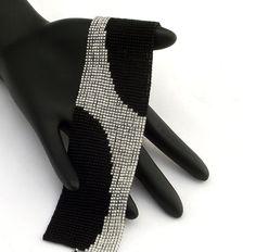 Ce bracelet comprend un balayage des perles delica cristal bordée dargent sur fond noir mat. Le bracelet est fini avec un fermoir en étain plaqué argent antique. Ces bracelets se faire remarquer. Chaque perle dans cette pièce est cousue dans lunité pour un produit fini qui se comporte comme un morceau de tissu et est tout aussi confortable à porter. • Largeur - 37mm ou 1.4 • Longueur incluant le fermoir - 180mm ou 7 » • Fermeture - Antique plaqué argent étain fermoir anneau et barre…