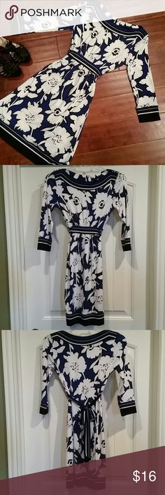 Fab Floral New York & Company Dress, Size XS A fabulous fun floral New York & Company Stretch dress, size XS. Print is black, white, and a beautiful royal blue. 3 silver buttons on each shoulder. Made of polyester/spandex for stretch and comfort. Sleeves and hem trimmed in stripes. Attached fabric belt ties in back. Super cute dress for work or a dinner out! Smoke-free and pet-free household. New York & Company Dresses