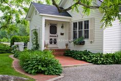 Curb appeal, shaded front entrance porch of house with hostas and daylilies planted, windowbox, white house with pink shutters and door, climbing vine, lawn, stone pebble drive, hedges, trees, garden landscaping...love the pale pink door & shutters!