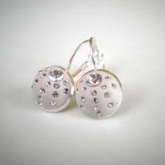 Náušnice s šatony Swarovski bílé Náušnice jsou zdobeny šatony Swarovski , které jsou zasazeny do bižuterní epoxidové hmoty bílé barvy. Velikost lůžka náušnice: průměr 12 mm. Bižuterní komponenty: barva stříbrná, bižuterní kov bez obsahu niklu.