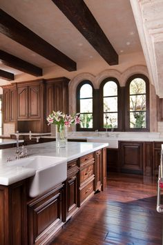 Wood kitchen with beamed ceiling, hard wood floors and white counter tops Dark Wood Kitchen Cabinets, Backsplash With Dark Cabinets, Dark Wood Kitchens, Wood Floor Kitchen, White Countertops, Kitchen Flooring, Kitchen Backsplash, Kitchen Island, Custom Kitchens