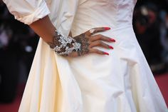 Rihanna's tattooed hand on the red carpet of the Cannes Film Festival, with red long nails adorned in diamond hand jewels, bracelets and a ring. For glamour celebrity fashion Cannes Film Festival red carpet jewellery spotting travel here: http://www.thejewelleryeditor.com/jewellery/top-5/best-red-carpet-jewellery-jewelry-cannes-film-festival-2017-weekend/ #jewelry