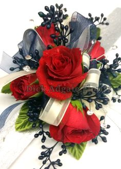 Red sweetheart roses with navy blue seeded eucalyptus and navy blue and creme ribbons. Prom / Homecoming flowers on a wrist corsage. Dick Adgate Florist original.