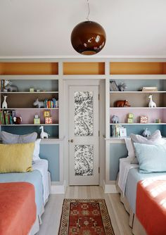 two twin beds with bookshelf headboards color blocking patterned wallpaper on paneled door Alexandra Loew