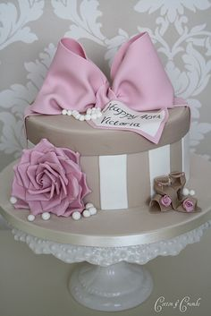 "Grey and white striped vintage ladies' hatbox topped with a large lilac bow and pearls, the tag reading, ""Happy 40th Birthday Veronica."" Loose pearls and a lilac rose adorn the base. Classy retro throwback style."