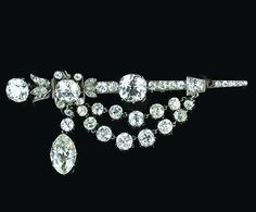 A late Victorian diamond brooch, circa 1890,  the stylised rapier with foliate decoration at the hilt set throughout with cushion-shaped, old brilliant and rose-cut diamonds, the three principal stones weighing 2.05, 1.28 and 1.18 carats, suspending swags of similarly cut stones and a marquise-cut diamond drop weighing 2.08 carats, one diamond deficient, mounted in silver and gold, length 6.8cm.