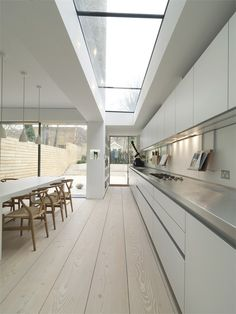 white, blonde wood + stainless steel #minimalist    That skylight is incredible as are the chairs and surfaces. #metal #modern #lifestyle