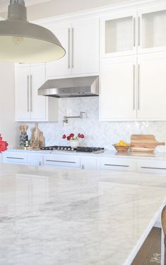 white modern farmhouse kitchen wooden finger bowl white carrar marble white shaker cabinets farmhouse pendants marble herringbone backsplash-2
