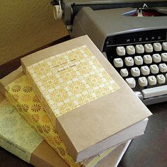 paper bag-covered books with title typed onto decorative paper