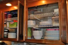 RV cabinet storage, metal shelves turned upside down so lip will keep items in place better.