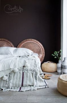 A lovely Moroccan wedding blanket and copper tea trays as decor up against the dark wall.