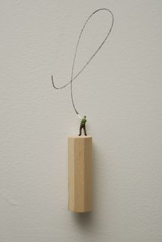 Man Drawing (green hat and vest) (2009), Object size: 4 in., Wooden Base, metal figurine, pencil drawing on wall.