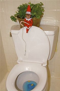 elf fishing for gold fish in the toilet bowl w/a  candy cane pole...
