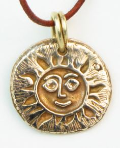 """Southwestern Sun design necklace. This sunny design represents the ever present sunshine in Tucson, Arizona. Wear this pendant to attract positive energy and help guide you through Life's path.    Bronze - Del Sol series Artisan handcrafted in sunny Tucson, Arizona. Adjustable leather cord necklace included.    Pendant is approx. 1"""" x 1"""" in diameter."""