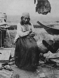 Puget Sound area woman sits near baskets and canoe, Washington, ca. 1903.