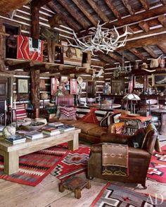 Colorado Saloon - In the adjacent saloon, a vintage English club chair and a sofa covered in a Ralph Lauren Home leather are grouped with a bespoke cocktail table atop antique Navajo rugs.