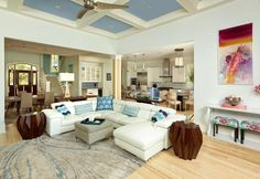 A living room featuring a coffered ceiling, cream sectional sofa, and substantial wood end tables. Design by http://dlbcustomhomedesign.com/