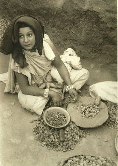 Woman shelling almonds to be sold in the market. Dades Valley,1950.