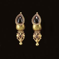 A PAIR OF ROMAN GOLD AND GARNET EARRINGS   Circa 2nd Century A.D.   Each boat-shaped, tapering at the ends to wires which form the closure, with a drop-shaped box attached to the front, set with a garnet, the box fringed with granulation, a small loop at the back, with a rigid pendant below composed of a cylinder with two rows of granulation, supporting an inverted pyramidal cluster of hollow spheres, ornamented with bezel-set garnets framed by ribbon and smaller spheres