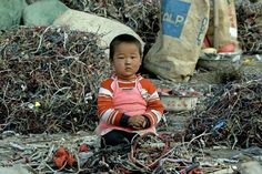 China Environment Kid Playing With Electronics.Over the last decade, China has become a global dumping ground for the world's discarded electronics. Above, a boy sits in a pile of waste at a scrapping ground.