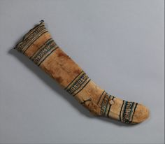 The Metropolitan Museum of Art  Sock  Date:     12th–13th century Geography:     Egypt, Fustat Culture:     Islamic Medium:     Cotton Dimensions:     H. 19 1/2 in. (49. 5 cm) W. 6 in. (15.2 cm) Classification:     Textiles Credit Line:     Rogers Fund, 1927 Accession Number:     27.170.95