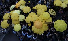 """HONGKONG-CHINA/OCCUPY Pro-democracy protesters carrying yellow umbrellas, symbol of the Occupy Central civil disobedience movement, are stopped by the police as they try to break the cordon line outside government headquarters in Hong Kong, China September 28, 2015. Monday marks the first anniversary of the Occupy Central or """"umbrella"""" movement, demanding universal suffrage in the territory. REUTERS/Bobby Yip"""