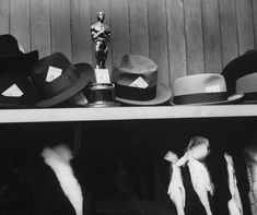 Producer Buddy Adler's Academy Award for From Here to Eternity stands amid hats in the coat check room at Romanoff's restaurant in Beverly Hills during an Oscars after-party in 1954.