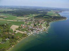 """Gstadt- Gollenshausen liegt direkt gegenüber der Fraueninsel am Chiemseeufer. Die ersten Touristen waren Pilger, denn die Lage bot schon immer günstige """"Gestadte"""" zur kurzen Überfahrt auf die Fraueninsel mit ihrem Kloster. Die Gäste von heute """"pilgern"""" nach Gstadt, um ebenfalls die Insel und den kleinen attraktiven Naturpark """"Hofanger"""" zu besuchen. Eine schöne Aussicht auf den See, die Chiemseeinseln sowie auf die Alpenkette hat man von dem Beobachtungsturm """"Ganszipfel""""."""