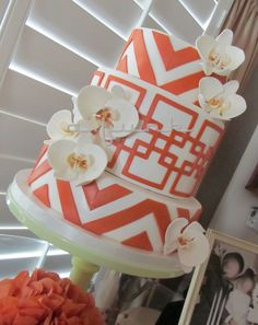 Modern patterns and color for my parents 40th anniversary cake! Inspired by the 70s with a more up to date look! Orange and white chevron pattern and overlapping squares are fondant. Gumpaste orchids, to honor the bride's bouquet. Amaretto Cake with Cherry SMBC, and fresh Cherries.  Thanks for looking!