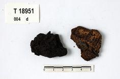"Textile fragment preserved by rust from Rødøy (Viking)(T18951d) "" Avlangt jernstykke med egg på den ene kanten (konkav) og rygg på den andre (konveks), trolig bruddstkr. av sigd eller ljå. I rusten sitter tekstilrester. Bev. l. 7,7 cm, st. br. 3,0 cm, st. t. ca. 0,7 cm."""