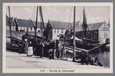 Een groep mensen, waarschijnlijk een 'vreemde' schipper met zijn vrouw poseren voor enkele vissersschepen op de helling. 1910-1930 #Urk