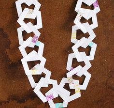 This Printable Pentagon Paper Chains tutorial is a twist on how to make paper chains. Rather than the traditional paper chain, this paper chain is created out of pentagon shapes connected together by strips of washi tape. Paper Doll Chain, Paper Chains, Paper Dolls, Free Printable Coloring Sheets, Free Printable Art, Free Printables, Diy Christmas Garland, Diy Garland, Garlands