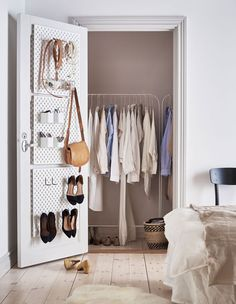 Valkoinen SKÅDIS-säilytystaulu on kiinnitetty vaatehuoneen oven sisäpintaan asusteita ja kenkiä varten