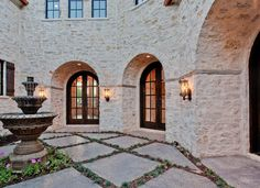 Cool Coral Stone Veneer mode Dallas Rustic Exterior Decorators with arch arch doors concrete pavers courtyard dark wood exterior lighting flowers fountain french doors Design Exterior, Rustic Exterior, Exterior Colors, Stone Exterior, Ranch Exterior, Stone Siding, Brick Restoration, Kitsch, Arched Doors