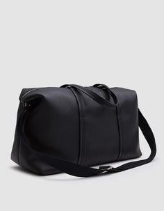Luxury travel bag from Maison Margiela in Black. Soft grain leather. Two-way top zip closure. Interior zip pocket. Adjustable grosgrain strap.Two top handles. Exterior pocket with magnetic closure. Silver-tone hardware. Signature exposed stitching detail.