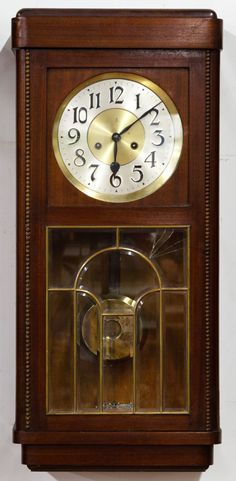 Lot 154: Mahogany Wall Clock by Gustav Becker; Having a leaded glass window, GB with crown mark on face, beaded accents, pendulum and key