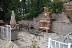 Stone fireplace built into retaining wall.  Tall wall broken into terraces.