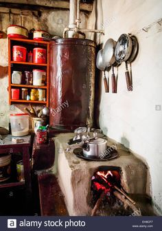 Pressure cookers on a clay stove in a guest house in the village of Ghami, Mustang, Nepal. Stock Photo