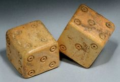 A PAIR OF ROMAN BONE DICE   CIRCA 1ST-4TH CENTURY A.D.   The cubes with incised dotted rings on each facet numbering 1 to 6   ½ in. (1.3 cm.) wide max.