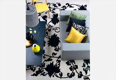 Pitadas de amarelo quebram a sobriedade do preto e branco e do cinza neste ambiente. A cadeira amarela tem design de Zanine Caldas