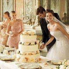 American model Emily Di Donato is cutting wedding cake in her wonderful wedding dress from Pronovias
