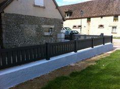Clôture barreaudée gris anthracite avec lames verticales, installée sur muret béton