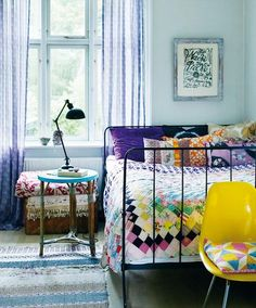 A colorful bedroom with a wrought-iron bed, quilted bed spread, a retro yellow plastic chair and lavender walls. The contrast between yellow and lilac is a really powerful way to bring good color dynamics into your decor.