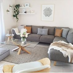 Dark Gray Couch with White Walls and Slate/Tan Accents.