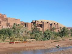Description  Aït Benhaddou along river bank Date  14 December 2005 (upload date) Source  Own work Author  Donar Reiskoffer ~`~ Aït Benhaddou is an ighrem (fortified village in English) (ksar in Arabic), along the former caravan route between the Sahara and Marrakech in present-day Morocco. They are a great example of Moroccan earthen clay architecture. Aït Benhaddou has been a UNESCO World Heritage Site since 1987.