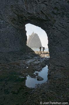 Hikers peer through the Hole in the Wall at Rialto Beach, La Push, Washington