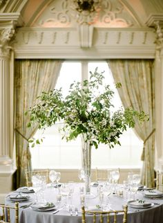 Tall centerpiece - original inspo. We can do a gold medium size pedestal with green branches, seasonal greens, and white limoinium or white monte christo ffiller flowers throughout to achieve a similar more wild look that will have a flower touch to it. These would cost about $150 each