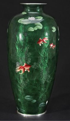 A large ginbari cloisonné enamel vase Ando Jubei Company, 20th century The slender ovoid body decorated in transparent and opaque enamels with brightly colored goldfish swimming in a pond with flowering lilies and waterweeds, portions of the design seen through the translucent green enamel ground, the base with the company mark, silver rims (star cracks, restorations).