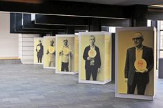 Large-scale graphics of people holding up the label identifying themselves, yellow and black exhibition design